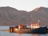 Ein alter Kutter liegt im stillen Fjordwasser