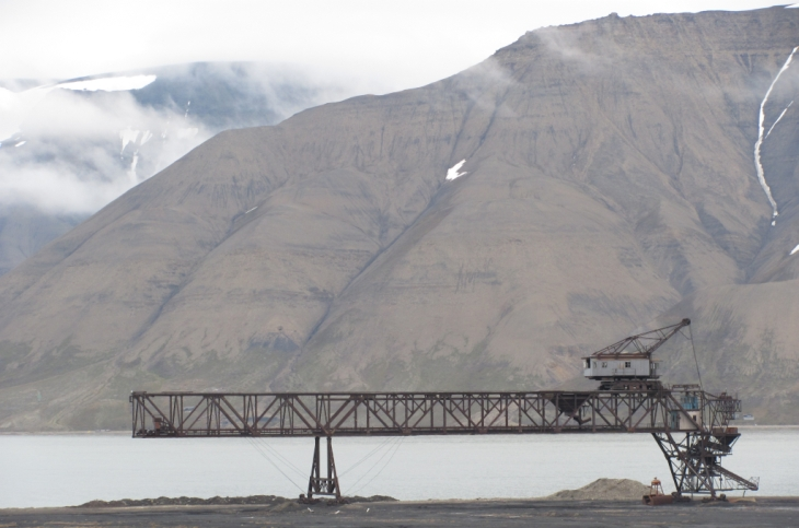 Ohne Worte: Ein alter Verladekran steht rostend am Adventfjord